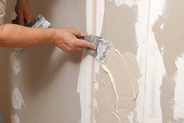 An showing us applying plaster to a wall